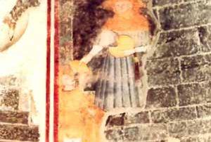 """Gravedona (CO) – Diocesi di Como - Chiesa di Santa Maria del Tiglio (XIV secolo) Abside settentrionale: frammento di affresco parietale del XIV secolo raffigurante San Lucio, in abito corto con mantello e cappello a spioventi, nell'atto di donare una fetta di formaggio con la mano destra, mentre sorregge, con la sinistra, la forma. La presenza del dipinto è spiegabile col fatto che a Gravedona """"ab immemorabili"""" si tiene l'11 e il 12 di settembre una grossa fiera di bestiame cui affluivano anche dalla Valtellina e dalla Bergamasca (M. B. Zecchinelli)"""