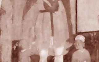 """Carona (Luganese) – Diocesi di Lugano - Chiesa di Santa Marta, dipinto murale (1486 ?) A destra dell'odierna porta di ingresso, al di sotto di un affresco rappresentante un """"Ecce homo"""" si scorgono le tre immagini dei santi Bernardo, Antonio Eremita e Lucio. L'affresco tardo-gotico rappresentante San Lucio è, con ogni probabilità, databile al 1486 e viene attribuito alla Bottega dei Seregnesi. San Lucio, con abito corto, mantello e cappello, è rappresentato con in mano un coltello, il cui ero pende alla cintola, ed una forma di cacio da cui sono stati tagliati i pezzi che si trovano nelle mani dei due poverelli che, come vuole la leggenda, sono sfamati dal pastore caritatevole. (A. Madesani)"""